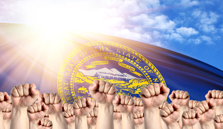 Labor Day concept with fists of men against the background of the flag State of Nebraska
