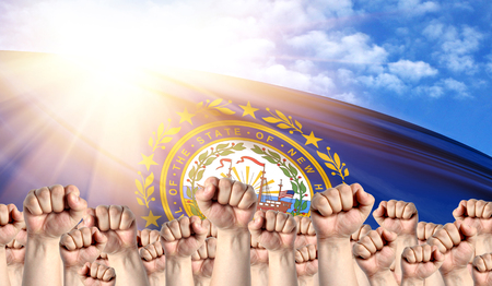Labor Day concept with fists of men against the background of the flag State of New Hampshire