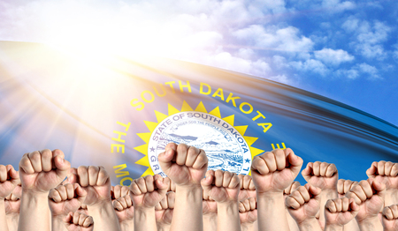 Labor Day concept with fists of men against the background of the flag State of South Dakota