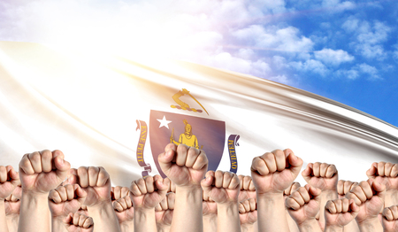 Labor Day concept with fists of men against the background of the flag State of Massachusetts
