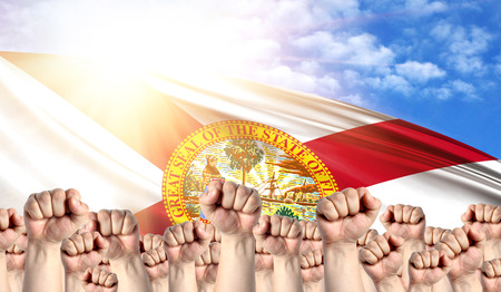 Labor Day concept with fists of men against the background of the flag State of Florida