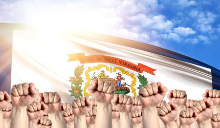 Labor Day concept with fists of men against the background of the flag State of West Virginia