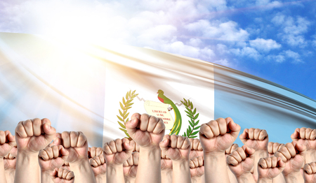 Labor Day concept with fists of men against the background of the flag of Guatemala