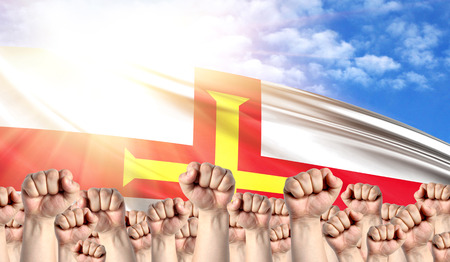 Labor Day concept with fists of men against the background of the flag of Guernsey