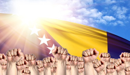 Labor Day concept with fists of men against the background of the flag of Bosnia and Herzegovina
