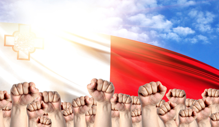 Labor Day concept with fists of men against the background of the flag of malta