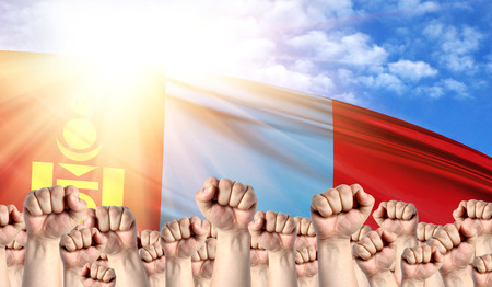 Labor Day concept with fists of men against the background of the flag of Mongolia
