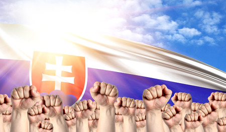 Labor Day concept with fists of men against the background of the flag of Slovakia