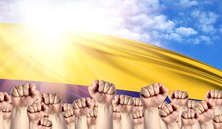 Labor Day concept with fists of men against the background of the flag of Colombia Stock Photo