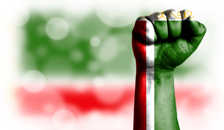 Flag of Chechen Republic painted on male fist, strength,power,concept of conflict. On a blurred background with a good place for your text.