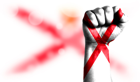 Flag of Jersey painted on male fist, strength,power,concept of conflict. On a blurred background with a good place for your text.