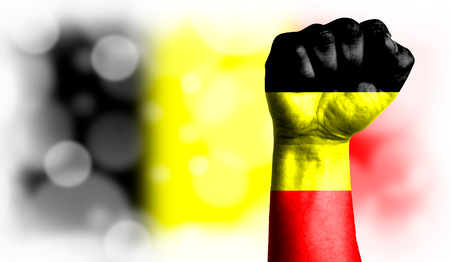 Flag of Belgium painted on male fist, strength,power,concept of conflict. On a blurred background with a good place for your text. Stock Photo