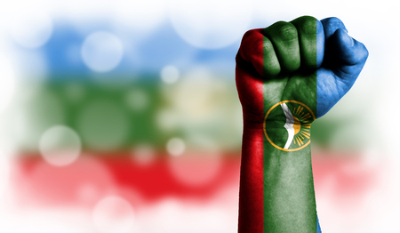 Flag of Karachay Cherkessia painted on male fist, strength,power,concept of conflict. On a blurred background with a good place for your text.