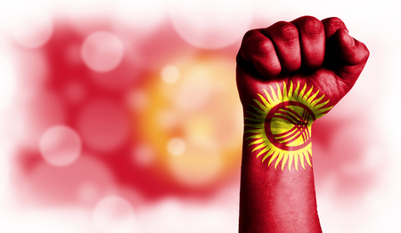 Flag of Kyrgyzstan painted on male fist, strength,power,concept of conflict. On a blurred background with a good place for your text. Stock Photo