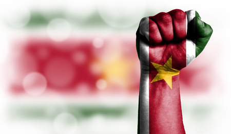 Flag of Suriname painted on male fist, strength,power,concept of conflict. On a blurred background with a good place for your text. Stock Photo