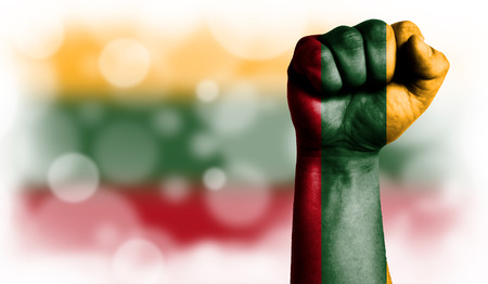 Flag of Lithuania painted on male fist, strength,power,concept of conflict. On a blurred background with a good place for your text.