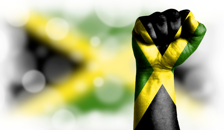 Flag of Jamaica painted on male fist, strength,power,concept of conflict. On a blurred background with a good place for your text. Stock Photo