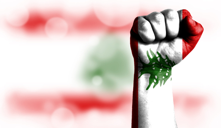 Flag of Lebanon painted on male fist, strength,power,concept of conflict. On a blurred background with a good place for your text.
