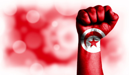Flag of Tunisia painted on male fist, strength,power,concept of conflict. On a blurred background with a good place for your text. Stock Photo