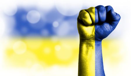 Flag of Ukraine painted on male fist, strength,power,concept of conflict. On a blurred background with a good place for your text.