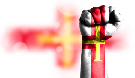 Flag of Guernsey painted on male fist, strength,power,concept of conflict. On a blurred background with a good place for your text.