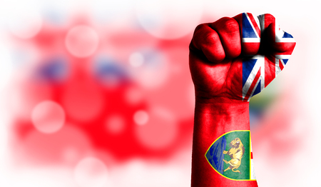 Flag of Manitoba painted on male fist, strength,power,concept of conflict. On a blurred background with a good place for your text.