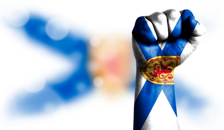 Flag of Nova Scotia painted on male fist, strength,power,concept of conflict. On a blurred background with a good place for your text.