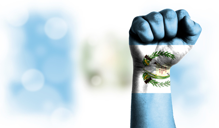 Flag of Guatemala painted on male fist, strength,power,concept of conflict. On a blurred background with a good place for your text.