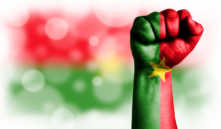 Flag of Burkina Faso painted on male fist, strength,power,concept of conflict. On a blurred background with a good place for your text. Stock Photo