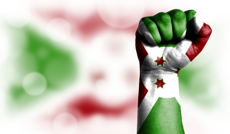 Flag of Burundi painted on male fist, strength,power,concept of conflict. On a blurred background with a good place for your text.