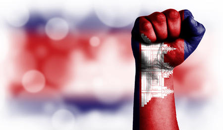 Flag of Cambodia painted on male fist, strength,power,concept of conflict. On a blurred background with a good place for your text. Stock Photo