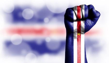 Flag of Cape verde painted on male fist, strength,power,concept of conflict. On a blurred background with a good place for your text.