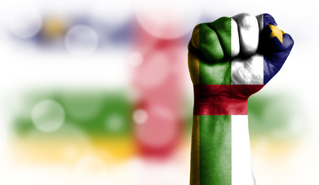 Flag of Central African republic painted on male fist, strength,power,concept of conflict. On a blurred background with a good place for your text. Stock Photo
