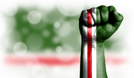 Flag of Chechen Republic of Ichkeria painted on male fist, strength,power,concept of conflict. On a blurred background with a good place for your text.