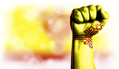 Flag of Chuvashia painted on male fist, strength,power,concept of conflict. On a blurred background with a good place for your text.
