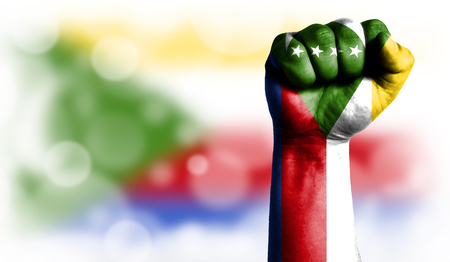 Flag of Comoros painted on male fist, strength,power,concept of conflict. On a blurred background with a good place for your text.