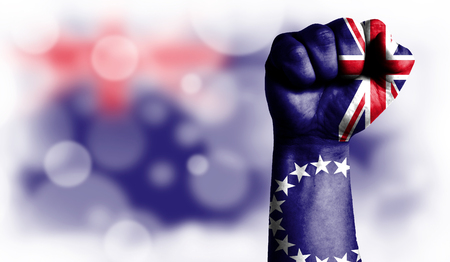 Flag of Cook Islands painted on male fist, strength,power,concept of conflict. On a blurred background with a good place for your text.