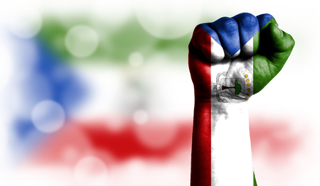 Flag of Equatorial Guinea painted on male fist, strength,power,concept of conflict. On a blurred background with a good place for your text.