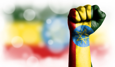 Flag of Ethiopia painted on male fist, strength,power,concept of conflict. On a blurred background with a good place for your text. Stock Photo