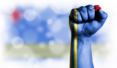 Flag of Aruba painted on male fist, strength,power,concept of conflict. On a blurred background with a good place for your text. Stock Photo