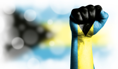 Flag of Bahamas painted on male fist, strength,power,concept of conflict. On a blurred background with a good place for your text.