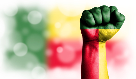 Flag of Benin painted on male fist, strength,power,concept of conflict. On a blurred background with a good place for your text.