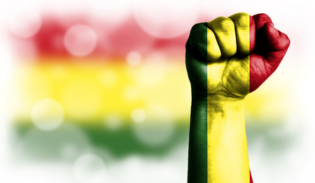 Flag of Bolivia painted on male fist, strength,power,concept of conflict. On a blurred background with a good place for your text.