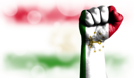 Flag of Tajikistan painted on male fist, strength,power,concept of conflict. On a blurred background with a good place for your text. Stock Photo