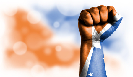 Flag of Tierra del Fluego Province Argentina painted on male fist, strength,power,concept of conflict. On a blurred background with a good place for your text.