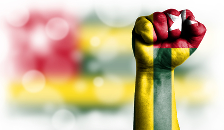 Flag of Togo painted on male fist, strength,power,concept of conflict. On a blurred background with a good place for your text. Stock Photo