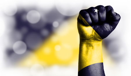 Flag of Tokelau painted on male fist, strength,power,concept of conflict. On a blurred background with a good place for your text.