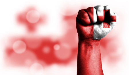 Flag of Tonga painted on male fist, strength,power,concept of conflict. On a blurred background with a good place for your text.
