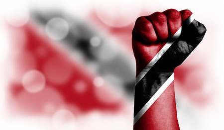 Flag of Trinidad and Tobago painted on male fist, strength,power,concept of conflict. On a blurred background with a good place for your text.