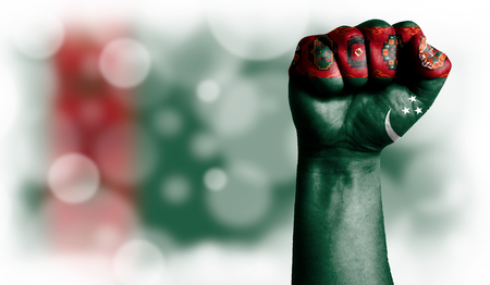 Flag of Turkmenistan painted on male fist, strength,power,concept of conflict. On a blurred background with a good place for your text.